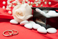Wedding rings and favors on elegant fabric background Stock Images