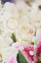 Wedding rings in flowers gold bouquet of white and pink Stock Image