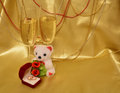 Wedding rings glasses with sparkling wine plush bear on a golden background a composition valentine s day satin drapery decorated Royalty Free Stock Photo