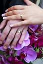 Wedding Rings and Hands Over Bridal Bouquet Royalty Free Stock Photo