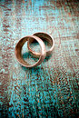 Wedding rings on old wood used grungy blue background with strong contrast Royalty Free Stock Photography