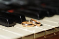 Wedding rings and piano on white keys of Royalty Free Stock Images