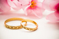 Wedding rings and pink flowers background Royalty Free Stock Photo