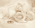 Wedding rings and roses. In Sepia toned. Retro style Royalty Free Stock Photo
