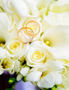 Wedding rings and roses two lie on a bouquet of light pink are golden Stock Images
