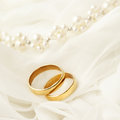 Wedding rings two golden on bridal dress Stock Images