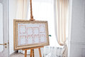 Wedding seating chart on the easel at light restaurant. Royalty Free Stock Photo