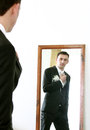 Wedding serious handsome bridegroom looking in mirror straightening his tie Royalty Free Stock Photography