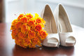 Wedding shoes and bouquet of orange roses nobody Royalty Free Stock Photos