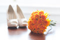 Wedding shoes and bouquet of orange roses nobody Stock Photo