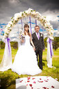 Wedding under arch happy newlywed couple standing in Stock Photography