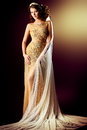 Wedding veil stunning woman in luxurious golden dress and a posing over dark background Stock Photography