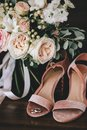 Wedding velvet pink shoes with gold wedding rings beside a bouquet of white roses, eucalyptus on a dark wooden background Royalty Free Stock Photo