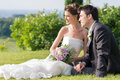 Wedding vision at the future portrait of happy married young couple sitting on grass Royalty Free Stock Image