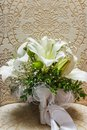 Wedding white bride shoes with a bouquet of white roses and other flowers, wedding rings on a stool Royalty Free Stock Photo