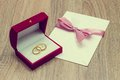 Weddings ring and invitation on woodern table Stock Images