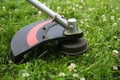 Weed trimmer mowing the grass with Stock Photo