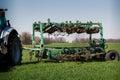Weeding machine behind tractor on green wheat field big wheels Stock Image
