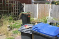 Weeding in progress there is evidence of going on this small garden with a full green bin and a small pair of cutters the Royalty Free Stock Photography