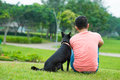 Weekend in the park back view of an owner sitting on green lawn with his black dog Royalty Free Stock Images