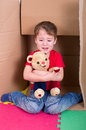 Weeping boy with teddy bear small crying in a cardboard box Stock Images