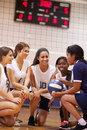 Weiblicher highschool volleyball team have team talk from trainer Lizenzfreie Stockfotografie