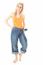 Weight loss - happy woman in too great trousers Royalty Free Stock Photography