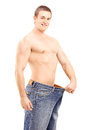 Weight loss muscular man in a big pair of jeans isolated on white background Stock Photo