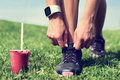 Weight loss runner tying laces with smoothie fresh start on fruit wearing smartwatch for cardio detox clean eating and diet woman Stock Photo