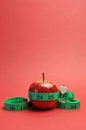 Weight loss slimming diet concept apple & tapemeasure - vertical. Stock Photo