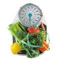 Weight loss vegetables on a bathroom scale with measuring tape symbolizing healthy diet for Royalty Free Stock Images