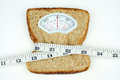 Weight scale with wholesome slice of bread and measuring tape on white background Stock Photos