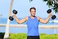 Weight training fitness man with dumbbell weights in workout outside fit muscular male lifting in shoulder press exercise Stock Photography