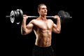 Weightlifting athlete lifting a barbell on black background Stock Photos
