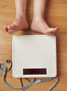 Weighty issue a white modern digital household scales lay on a clean wooden floor along with a blue unraveled tape measure next to Stock Photography