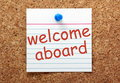 Welcome aboard the phrase printed on a lined index card and pinned to a cork notice board Stock Photo