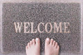 Welcome Door Mat With Female Feet. Friendly Grey Door Mat Closeup with Bare Woman Feet Standing. Welcome Carpet. Royalty Free Stock Photo