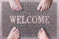 Welcome Door Mat With Funny Family Feet. Friendly Grey Door Mat Closeup with Four Bare Feet Standing. Four Feet on Royalty Free Stock Photo