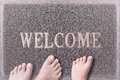 Welcome Door Mat With Three Feet. Friendly Grey Door Mat Closeup with Bare Feet Standing. Welcome Carpet. Royalty Free Stock Photo