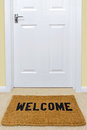 Welcome doormat outside a door in front of Royalty Free Stock Photography