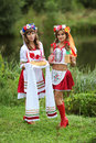 Welcome guest two girls in ukrainian costumes on the banks of the river with bread and vodka dressed up for the holiday of ivan Stock Photography