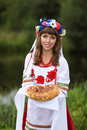 Welcome guest ukrainian girl in national clothes meets guests with handmade bread Stock Photo