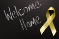 Welcome home the words written on a blackboard next to a traditional yellow ribbon Stock Photos