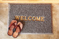 Welcome mat with brown sandals Royalty Free Stock Photo