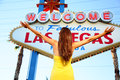 Welcome to fabulous las vegas sign woman happy tourist standing with arms raised out looking at nevada usa Royalty Free Stock Images