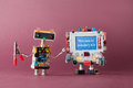 stock image of  Welcome to industry 4.0 concept. IT specialist robot with pliers looking colorful computer. The new economic future