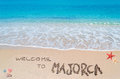 Welcome to majorca turquoise water and golden sand with shells and sea stars and written on it Royalty Free Stock Photo