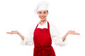 Welcome to my restaurant smiling young female chef standing with open palms warm gesture Royalty Free Stock Image