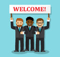 Welcome to our business team three businessmen of various nations are holding a sign saying Stock Photo