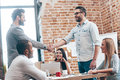 Welcome to our team two men shaking hands and smiling while their coworkers sitting at the table in office Stock Image